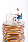 Online Money. Miniature figure sitting at desk with computer on top of stack of quarters Stock Image