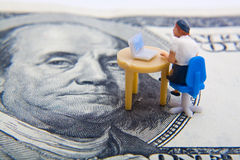 Online Money. Miniature figure sitting at desk with computer on top of hundred dollar bill Stock Photo