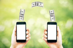 Online money transfer. Concept with two male hands holding smart phones with blank white screens and dollar bills above on abstract green background. Mock up Royalty Free Stock Photos