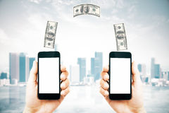 Online money transfer concept. With two male hands holding smart phones with blank white screens and dollar bills above on city background. Mock up, 3D Royalty Free Stock Image