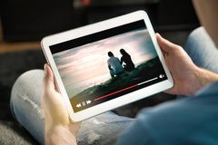 Online movie stream with mobile device. Man watching film on tablet with imaginary video player service stock photography