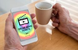 Online movie tickets buying concept on a smartphone. Male hands holding a smartphone with online movie tickets buying concept and a cup of coffee Stock Photo