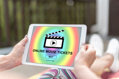 Online movie tickets buying concept on a tablet. Female hands holding a tablet with online movie tickets buying concept Royalty Free Stock Image
