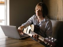 Online music school play guitar lessons. Online music school. young man learns how to play guitar through the internet. limitless possibilities for education Royalty Free Stock Photography