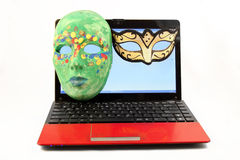 Online mystery dating. Masks  on a computer laptop screen, internet dating concept Royalty Free Stock Image