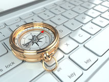Online navigation. Compass on laptop keyboard. Stock Photo