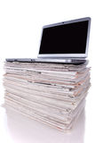 Online News. Laptop over a stack of newspapers for internet information access (isolated on white Stock Photos