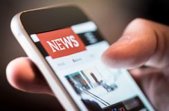 Online news in mobile phone. Close up of smartphone screen. Man reading articles in application. Hand holding smart device. Mockup website. Newspaper and royalty free stock image