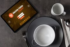Online order concept with tableware. Tablet with online order concept on a lain table stock photos