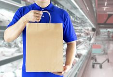 Online order grocery shopping concept. Delivery man hand holding packaging paper bag in blue uniform on supermarket background. Delivery service delivering stock photo
