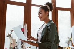 Online orders by email. Young woman tailor with laptop is answering emails. Online orders by email. Side view of young woman tailor with laptop is answering stock photos