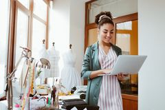 Online orders by email. Young woman tailor with laptop is answering emails. In design studio royalty free stock photos