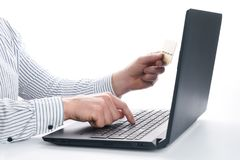 Online payment, Businessman`s  hands holding a credit card and using laptop Royalty Free Stock Photos