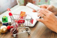 Online payment, Close up at gift boxes in shopping cart and Christmas decoration, woman hands using smartphone and laptop computer Stock Photo