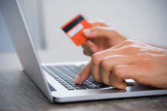 Online payment. Closeup hand of men typing credit card details on laptop to complete payment process. Close up of male hand paying bills online with laptop and royalty free stock image