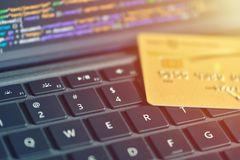 Online payment concept. Credit card on laptop keyboard, close-up angle view with warm sun lens flare. Computer code on screen stock photos