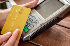 Online payment concept with credit card and terminal on wooden background Royalty Free Stock Photography