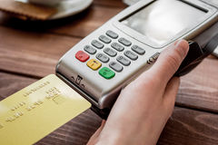 Online payment concept with credit card and terminal on wooden background Royalty Free Stock Images