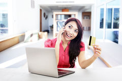 Online payment with credit card. An attractive woman purchasing product online using her laptop computer, credit card, and mobile phone, shot at home Stock Photos