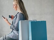 Online payment credit card smartphone copy space. Online payment. Young blonde woman with credit card shopping via smartphone. Copy space on grey background stock photography
