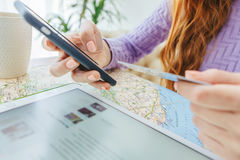 Online payment with credit card. Woman hands holding card and phone. Tablet on the table and Europe map. Travel mood Stock Image