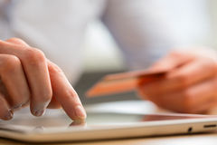 Online Payment by Credit Card. A young woman pays by credit card for an online purchase through a tablet computer Royalty Free Stock Photography