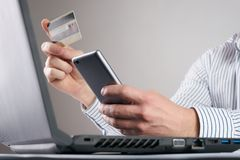Online payment, Man`s hands holding a credit card and using smart phone Royalty Free Stock Photography