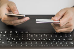Online payment,Man's hands holding a credit card and using smart phone for online shopping. Stock Photography