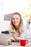 Online payment. Portrait of young blond woman making online payment of bills while using laptop and holding in her hand a bank card Stock Images