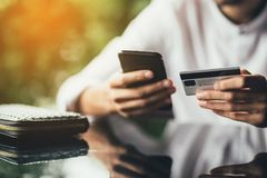 Online payment and shopping concept. male holding cell phone in one hand and credit card in other, making transaction. Suing mobile banking app during lunch at stock photos