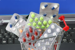 Online pharmacy. Trolley filled with pills labtop iin background Royalty Free Stock Photography