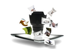 Online photography sharing and business. Modern portable tablet computer with a lens and lenshood on the surface of the screen surrounded by floating photographs Stock Image