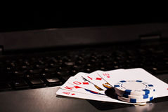 Online poker. On-line poker idea with straight flush and chips on top of the laptop Royalty Free Stock Images