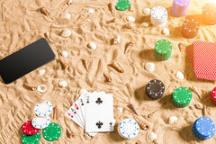 Online poker game on the beach with digital smart and stacks of chips. Top view Stock Images