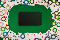 Online poker game with digital tablet, chips and cards royalty free stock image