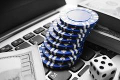 Online-poker i svart & vit med blåa pokerchiper, tärning & buntar av hundratals Arkivfoto