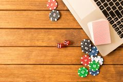 Online poker. Laptop, poker chips, dice, a deck of cards on a wooden table. Online casino concept royalty free stock photo