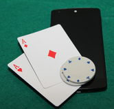 Online poker on mobile phone. Pocket aces on mobile phone with red chips on them stock image