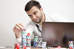Online poker stacking chips while smiling. Happy man , stacking chips, online poker win metaphor Stock Images