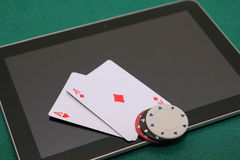 Online poker on tablet. Pocket aces on tablet with red, black and white chips on them royalty free stock photography