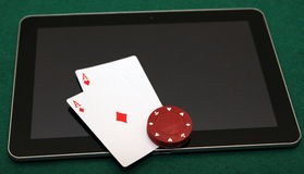 Online poker on tablet. Pocket aces on tablet with red chips on them stock photo