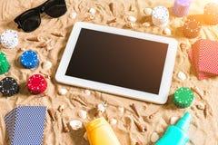 Online-pokerlek på stranden med den digitala minnestavlan och buntar av chiper Top beskådar Royaltyfri Bild