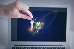 Online privacy information protection. Internet safety concept. Close-up of male hand is holding metal key. Screen of laptop with padlock icon on background Stock Photos