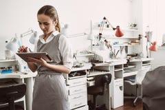 Online-produktion Nära övre stående av den unga kvinnliga juveleraren i förkläde genom att använda CRM systemet på hennes digital royaltyfria foton