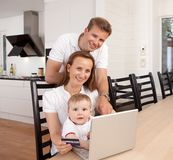 Online Purchase. Happy family looking at the camera with a smile making an online purchase Royalty Free Stock Images
