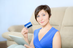 Online Purchase. Young woman sitting with digital tablet and holding a credit card stock photography
