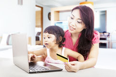 Online purchase. Young asian women online shopping using credit card with her daughter, shot at home Royalty Free Stock Image