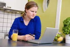 Online Purchase. A young female making an online purchase from her kitchen Royalty Free Stock Photography