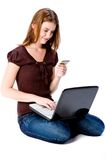 Online Purchase. A young attractive woman with laptop and credit card making online purchase Royalty Free Stock Photography