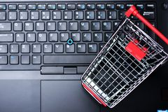 Online purchase and e-commerce concept with empty shopping trolley as symbol on laptop keyboard. Online purchase and e-commerce concept with empty shopping Royalty Free Stock Photo